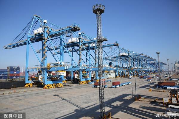 青岛港全自动化码头(二期)投产运营,一艘货轮在装卸货物。